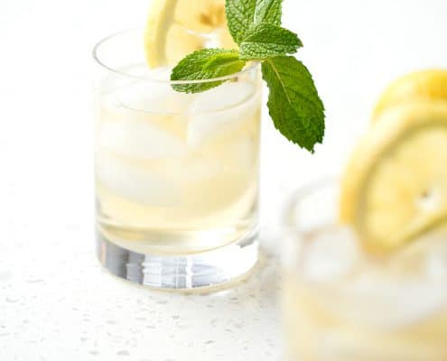 glass of green tea on which background with slice of lemon and mint sprig
