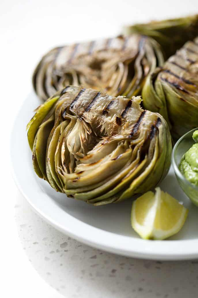 grilled artichokes halved on platter on white background
