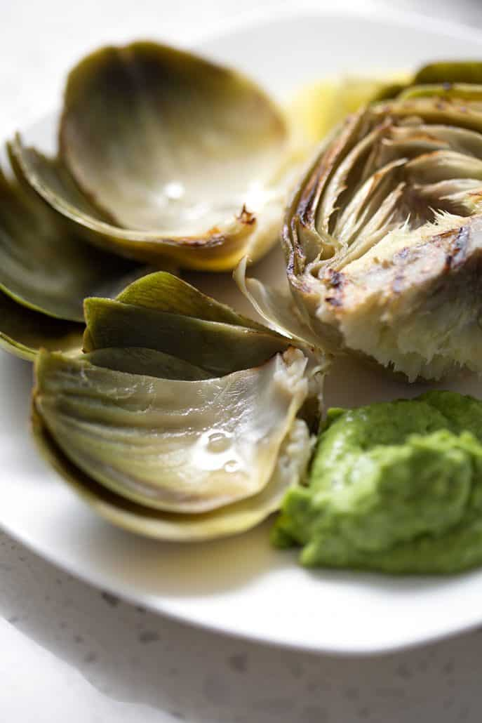 midway through eating an artichoke with dollop of green dip