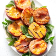 platter of grilled peaches garnished with mint