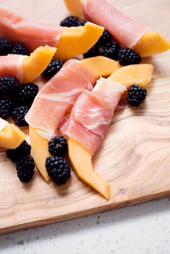 cantaloupe slices wrapped in prosciutto with blackberries on cutting board
