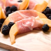 Cantaloupe slices wrapped in prosciutto with blackberries on a cutting board