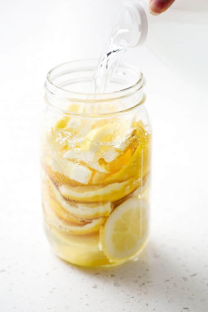 pouring vinegar over lemon rinds in mason jar on white background