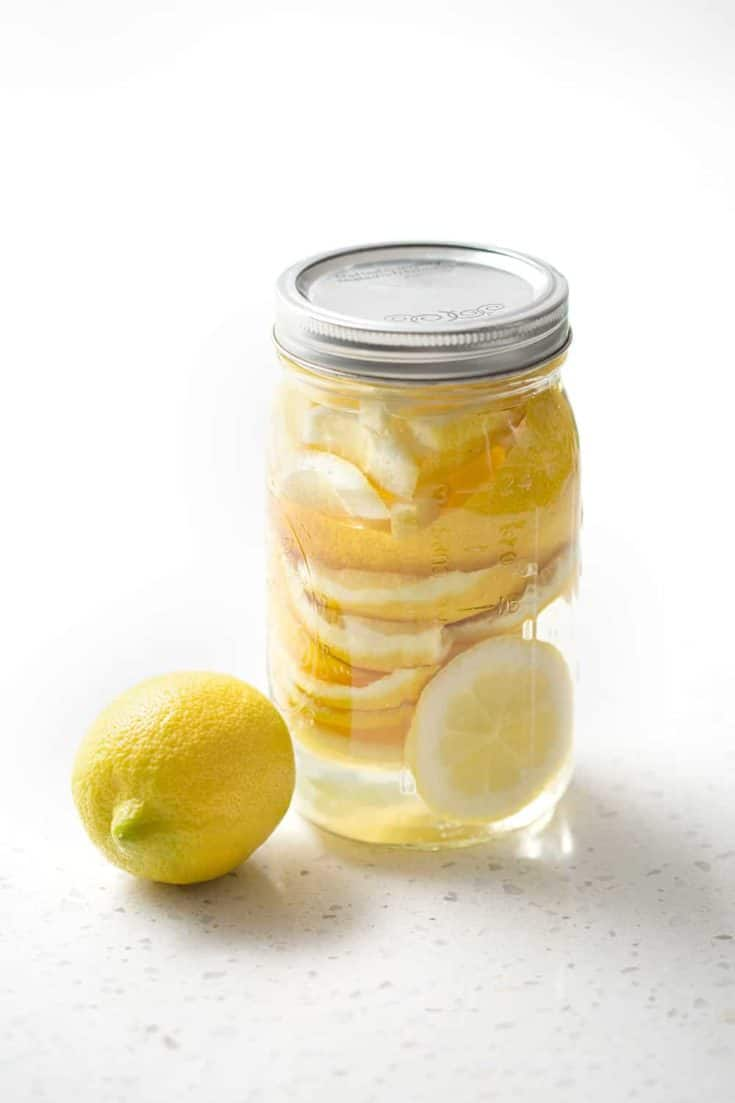 lemon rind in mason jar with vinegar on white background