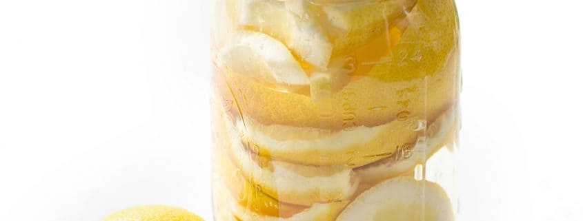 lemon rind in mason jar with vinegar on white background