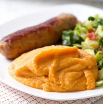 plate of mashed sweet potatoes, sausage and brussel sprouts