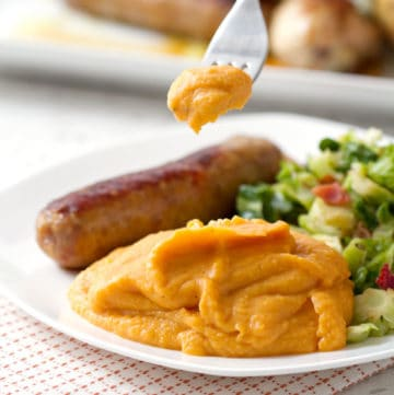 forkful of mashed sweet potato on plate with sausage and greens