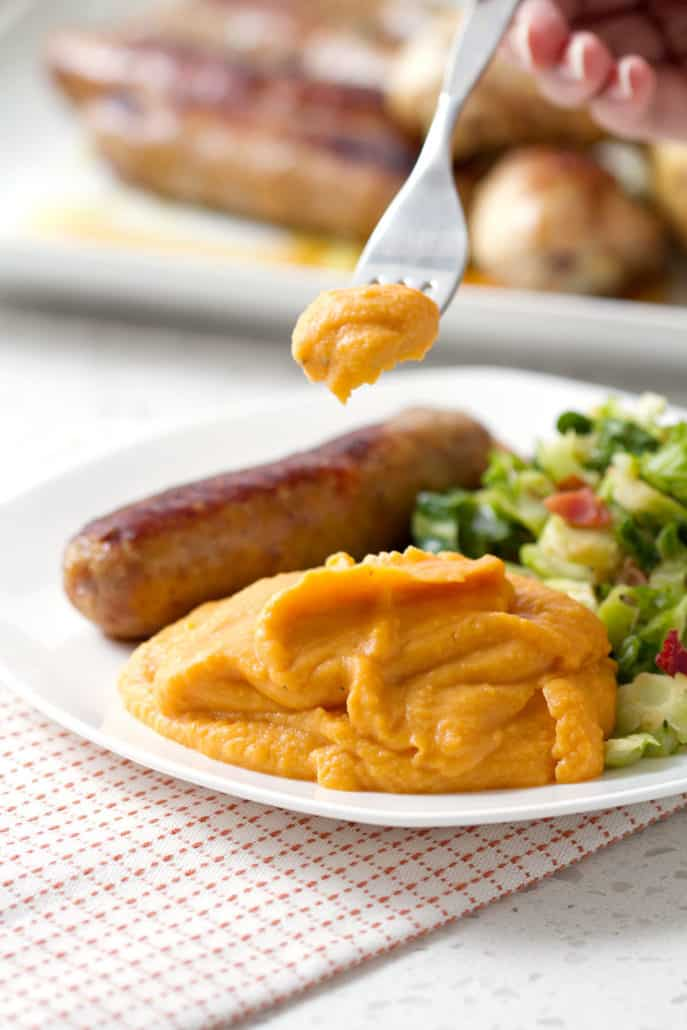 forkful of mashed sweet potatoes with plate of sausage and greens
