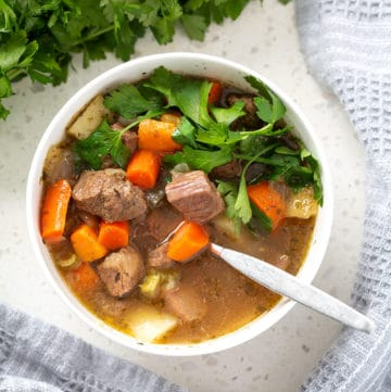 aip beef stew in bowl with spoon surrounded by parsley and towel from above