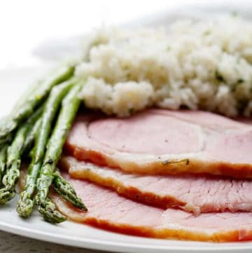 slices of ham on plate with rice and asparagus