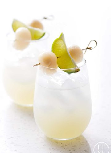 wine glass filled with drink and ice garnished with lime and lychee