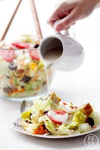 pouring salad dressing over plate of salad on white background