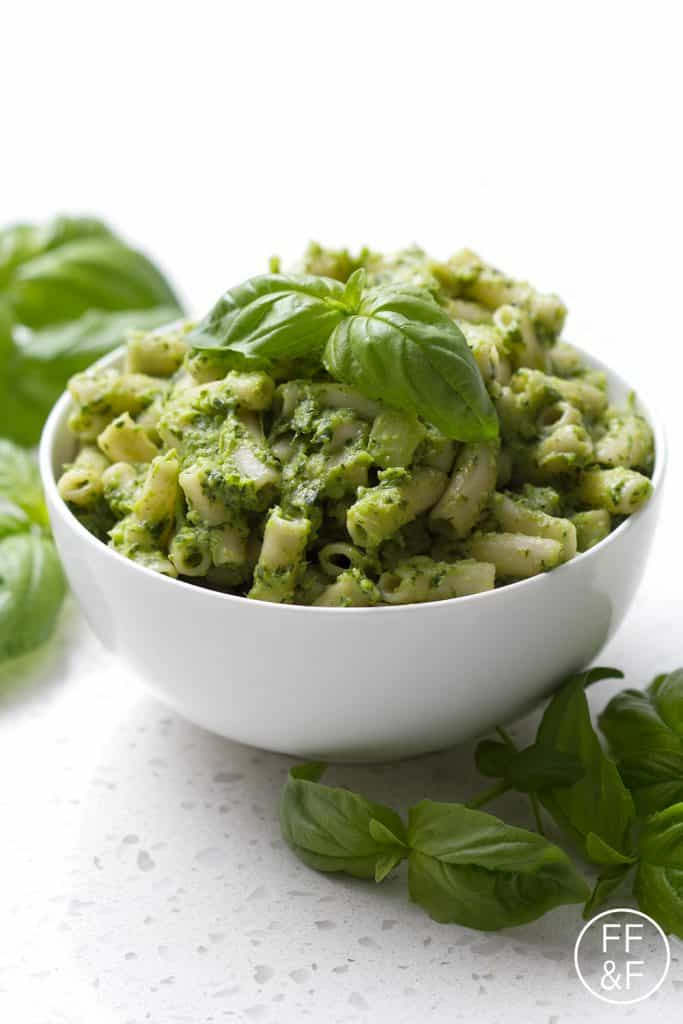 pesto pasta in bowl garnished with basil leaves