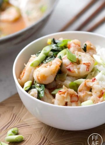 shrimp and basil in a bowl with chopsticks in the background