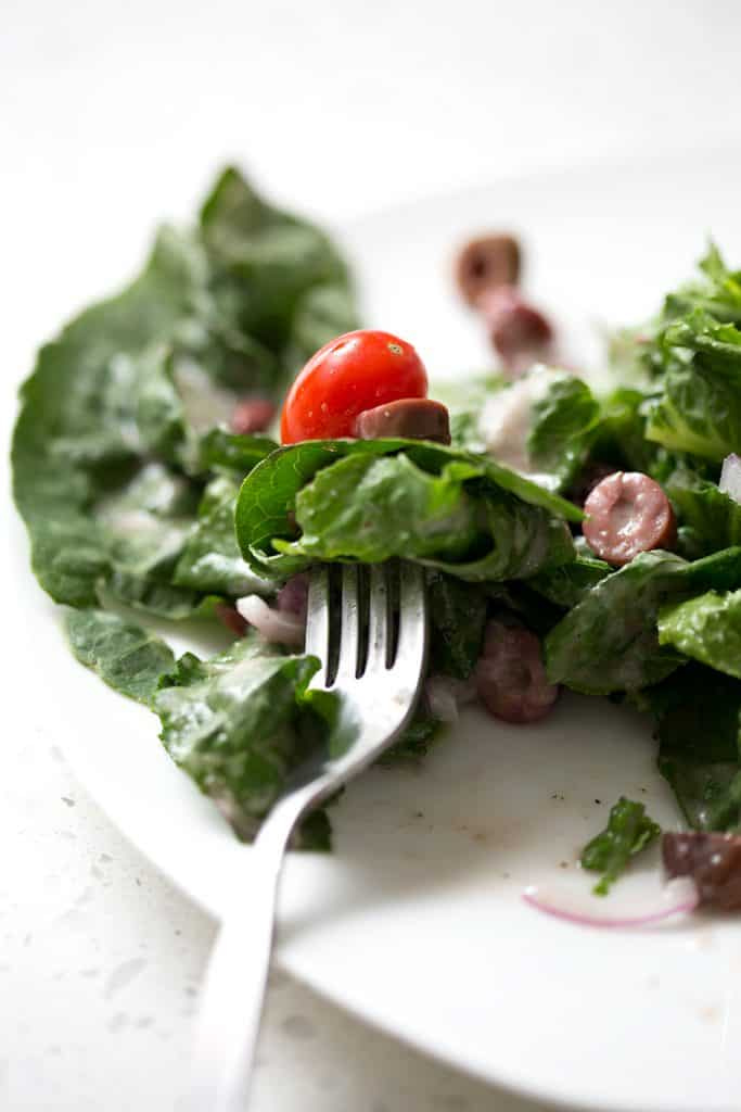 A simple recipe for an autoimmune protocol approved Mediterranean Salad. Romaine lettuce is the base for lots of onions, tomatoes, kalamata olives and homemade Mediterranean Salad Dressing. This recipe is allergy friendly (gluten, dairy, shellfish, nut, egg, and soy free) and suits the autoimmune protocol (AIP) and paleo diets.