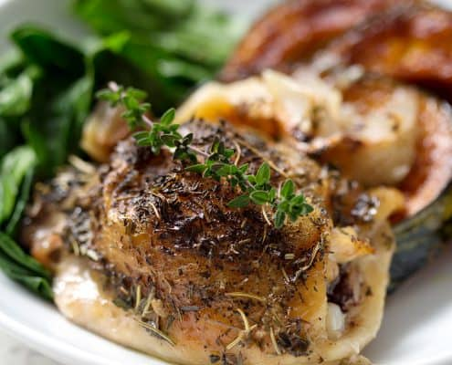 roast chicken garnished with thyme sprig on a plate with greens