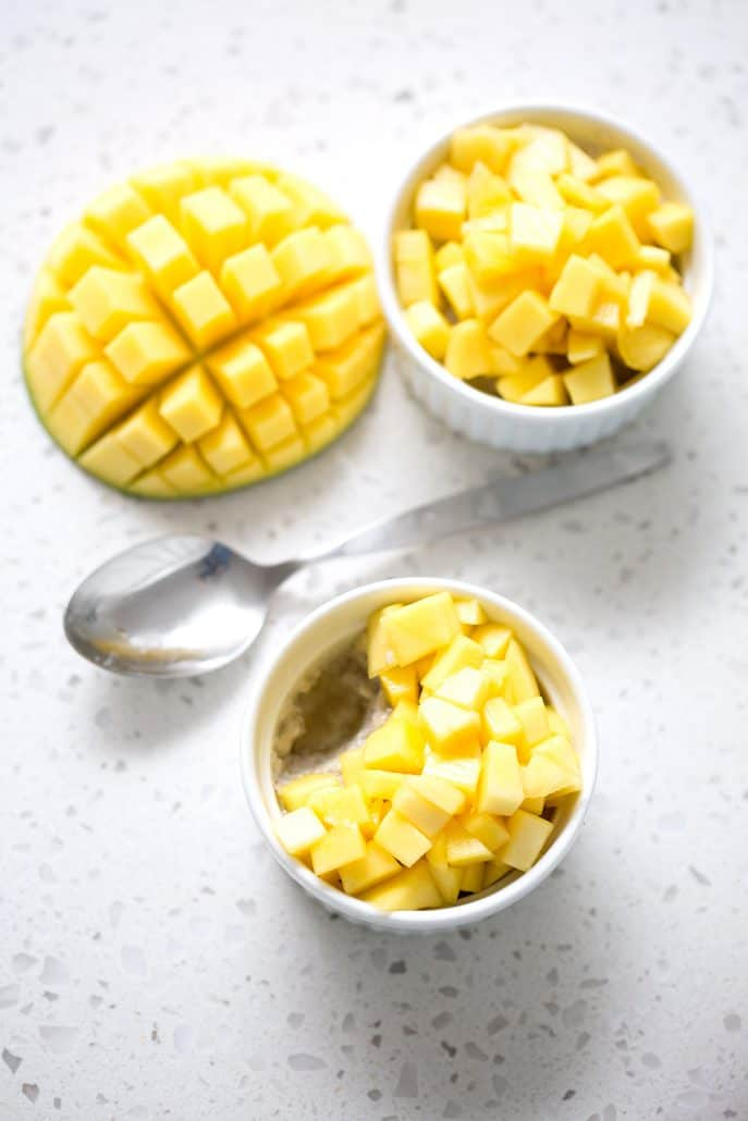 sliced mango with chopped mango in ramekins with spoon