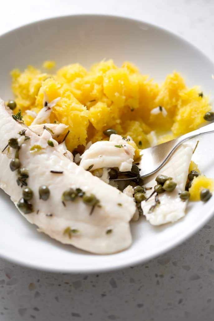 plate of mashed squash and fish with capers and seasonings with fork