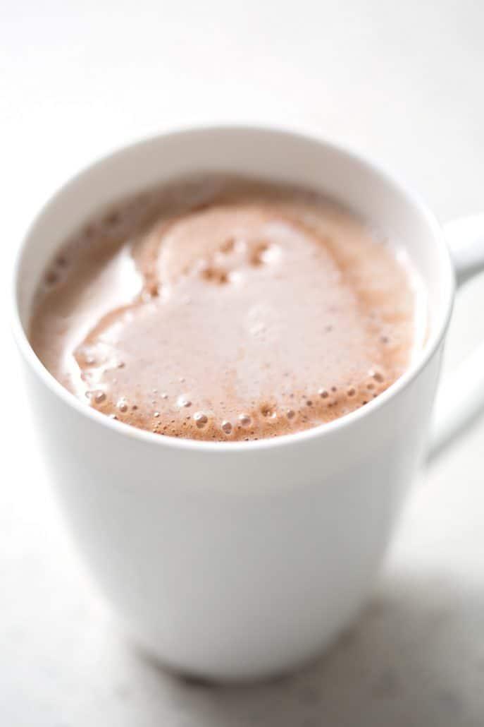 melting heart shaped chocolate marshmallow in mug on white background