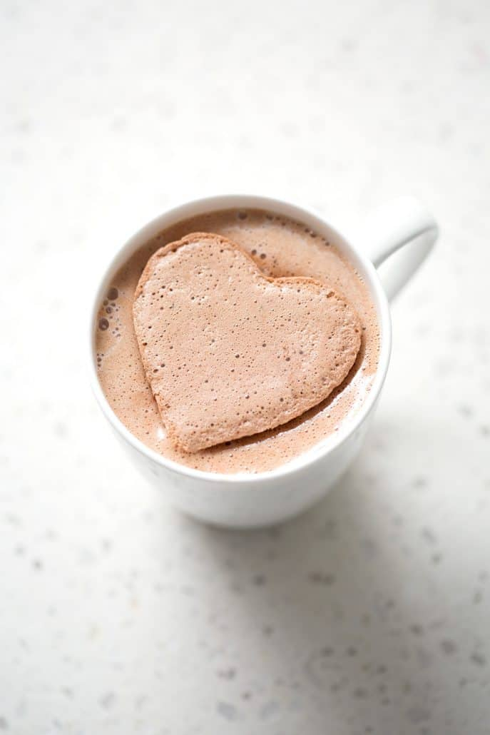 heart shaped chocolate marshmallows melting in mug on white background
