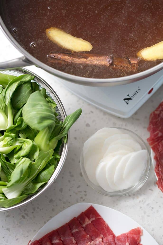 bok choy, daikon and raw meat around hot pot with cinnamon stick and slices of ginger