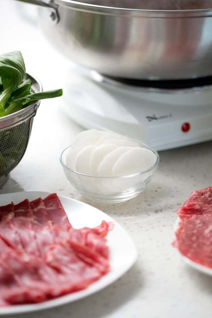 raw meat, daikon and bok choy in front of hot pot pan
