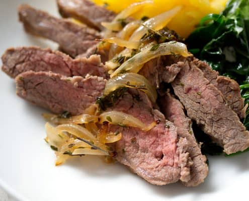 sliced flank steak with cooked onions, spinach and squash in bowl