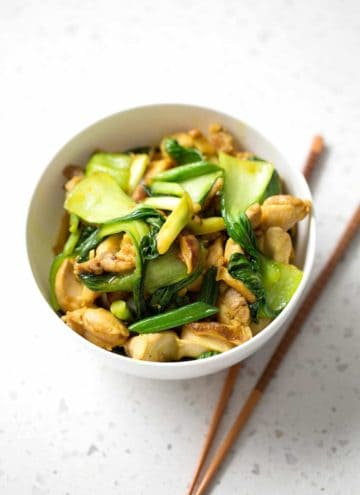 stir fry in white bowl with chopsticks on white background
