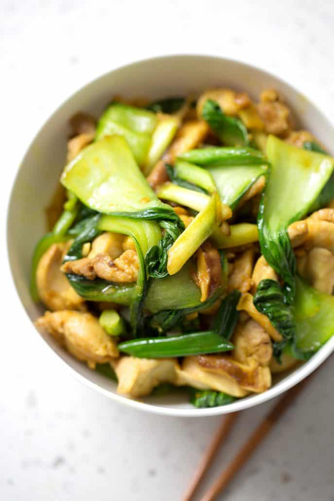 greens and chicken stir fry in white bowl with chopsticks on white background