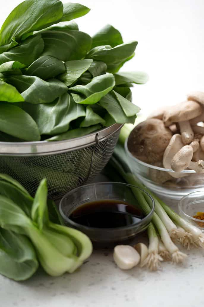 fresh bok choy, garlic, green onions and mushrooms on white background