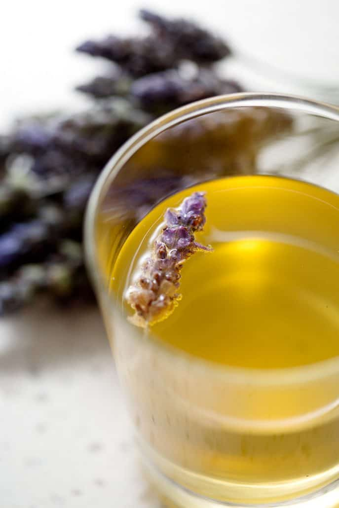 glass of kombucha tea with lavender flower floating in glass and bunches of lavender in the background
