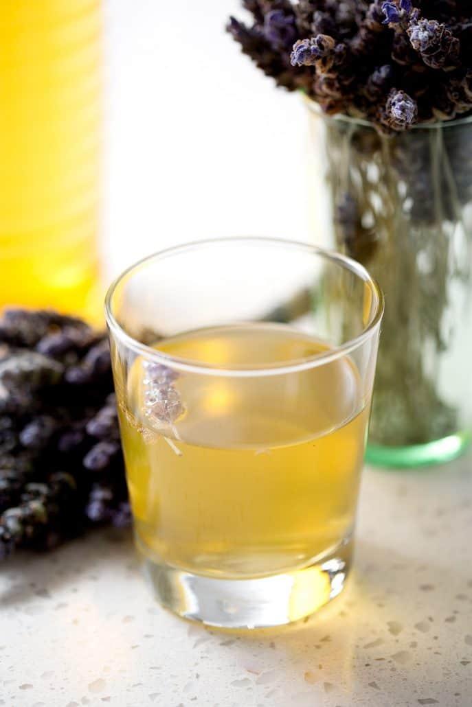 glass of kombucha tea with lavender bunches on white background