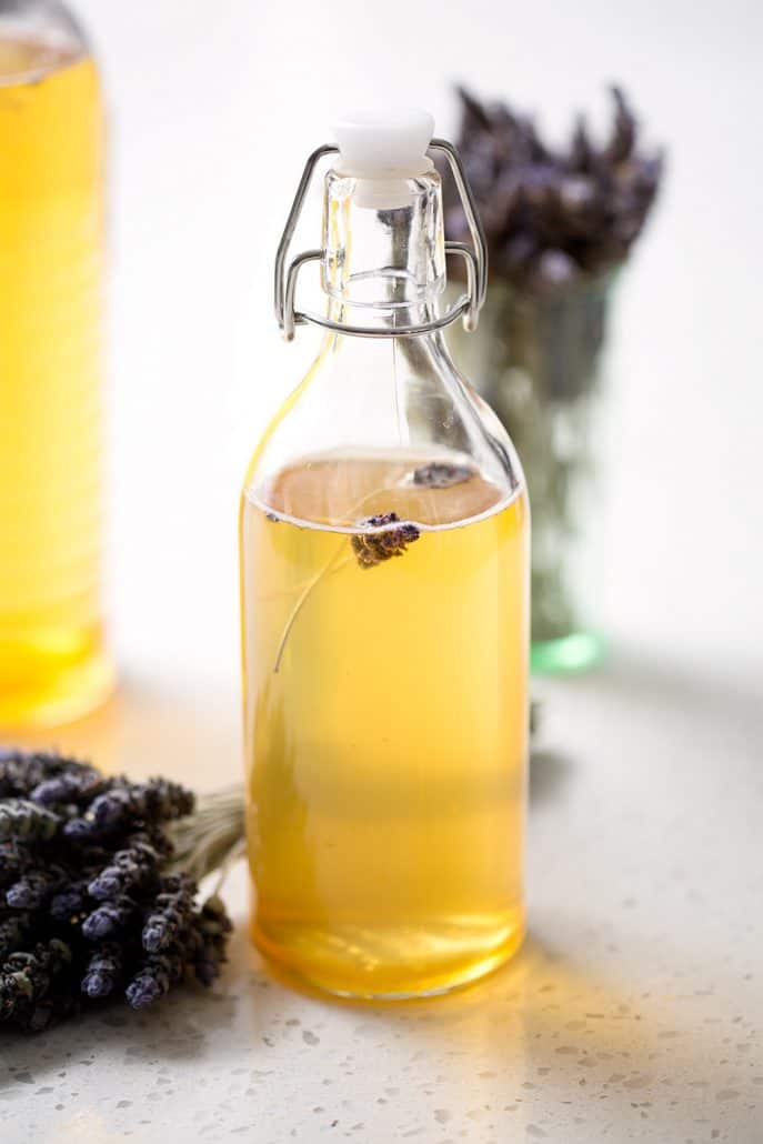 bottle of honey lavender kombucha tea with bunches of lavender on white background