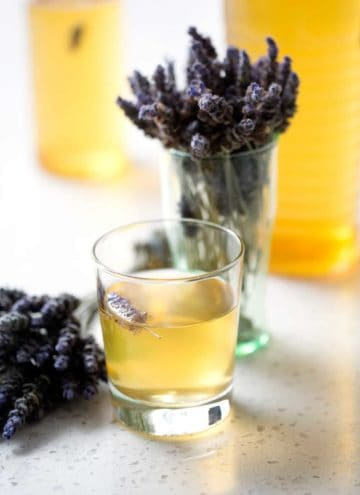glass and bottle of kombucha tea with bunches of lavender on white background