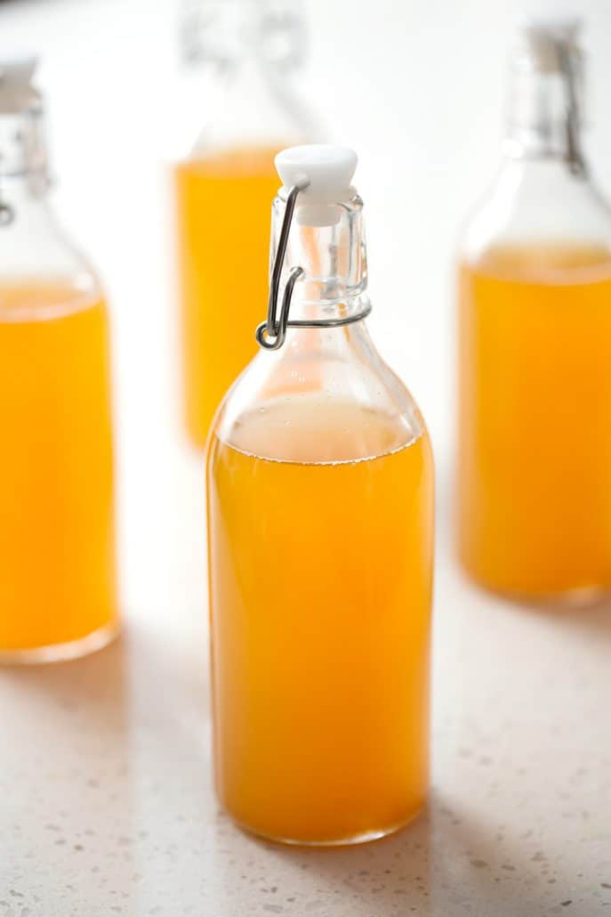 bottle of homemade mango kombucha tea on white background