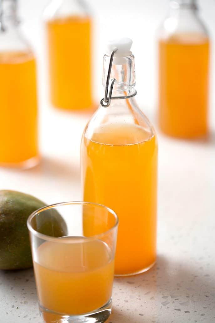 bottle and glass of homemade mango kobucha with mango on white background