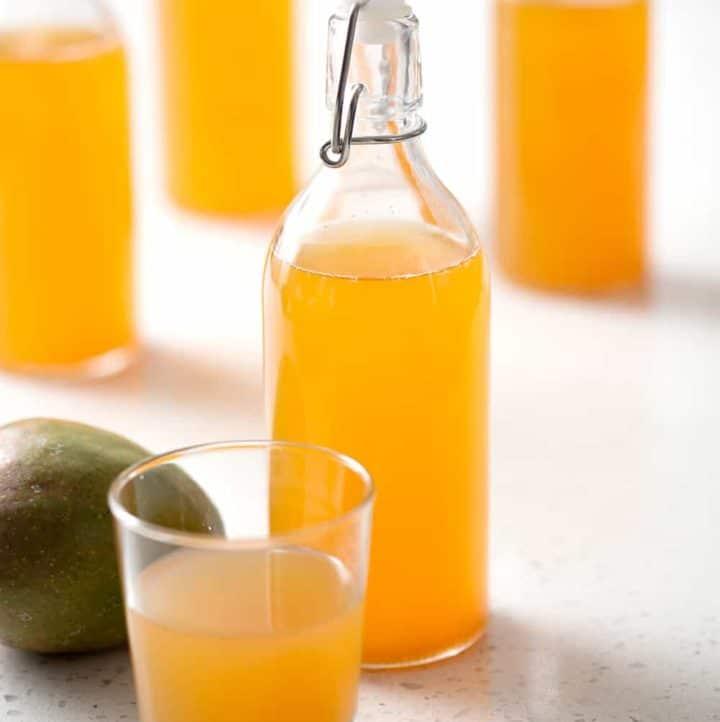 bottle of mango kombucha tea with mango on white background