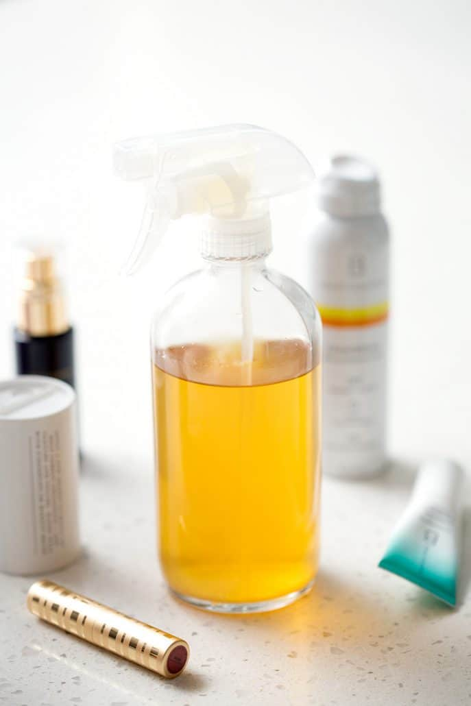 bottle of homemade household cleaner and other non-toxic products on white background