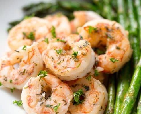 plate of seasoned shrimp with asparagus on white background