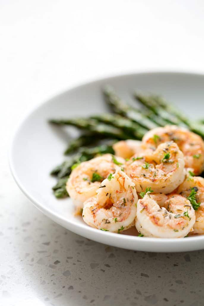 cooked and seasoned shrimp with asparagus pn white background