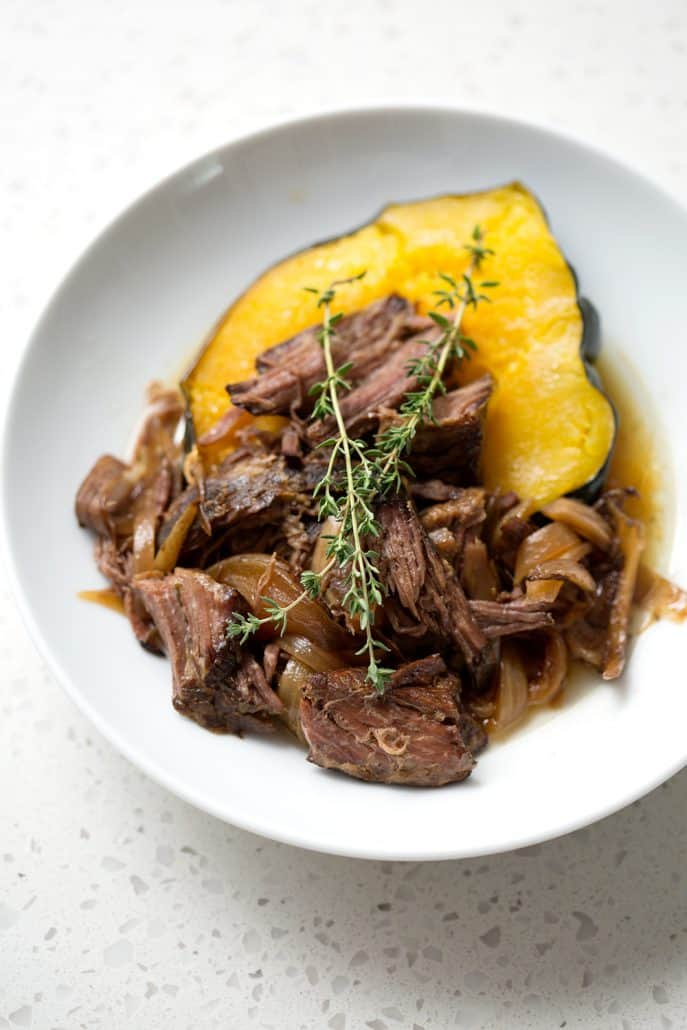 shredded beef on top of acorn squash with sprigs of thyme on white background