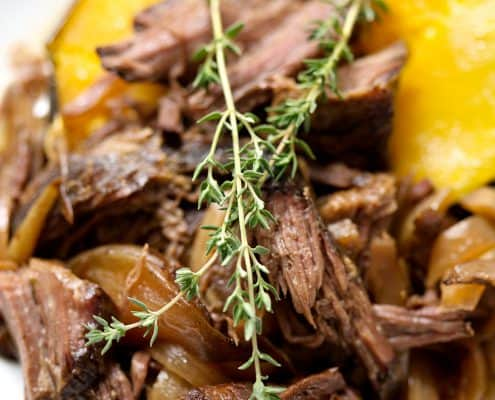 shredded beef on acorn squash with sprigs of thyme
