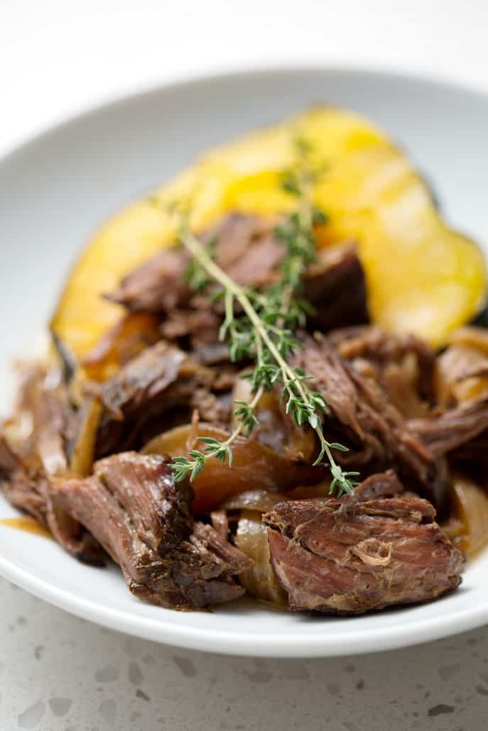 shredded beef on top of acorn squash with sprig of thyme