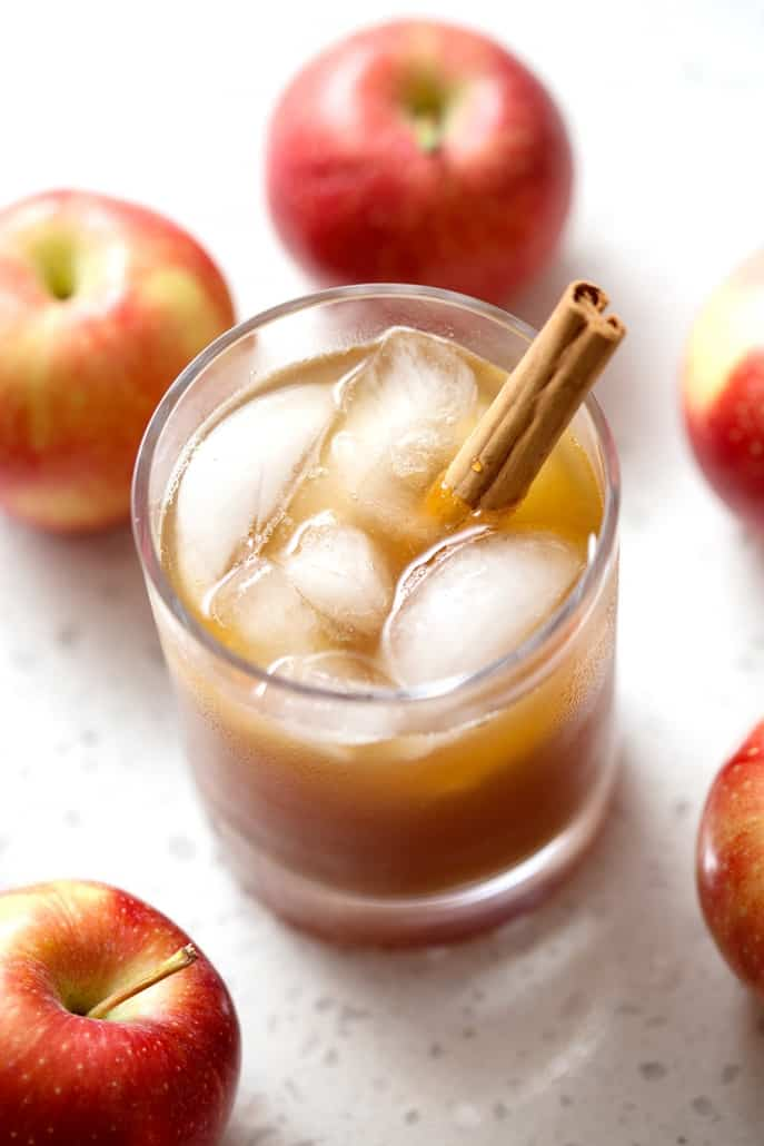 glass of kombucha with cinnamon stick surrounded by apples on white background