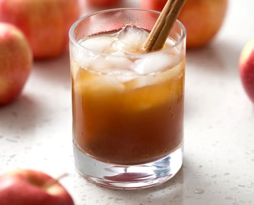 glass of kombucha in glass with apples and cinnamon stick on white background
