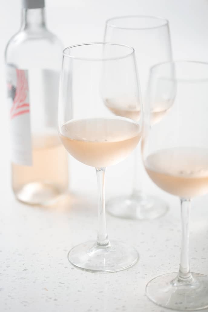 bottle of rose surrounded by glasses