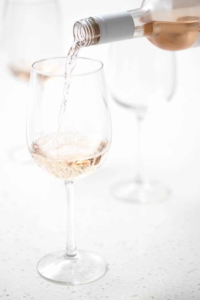 rose wine being poured into wine glass