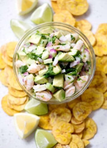 bowl of ceviche surrounded by plantain chips and lime