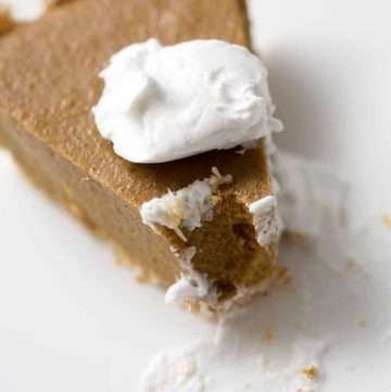 pie of pumpkin pie with dollop of cream on white plate