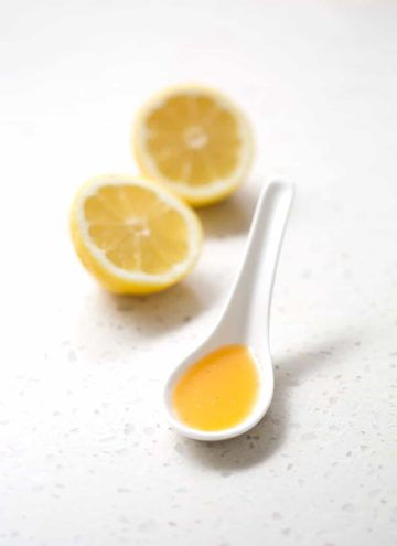 spoonful of juice with lemon halves on white background